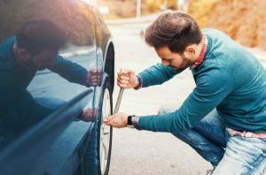 St Louis man changing flat tire