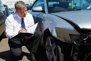 insurance adjuster examining car accident damage