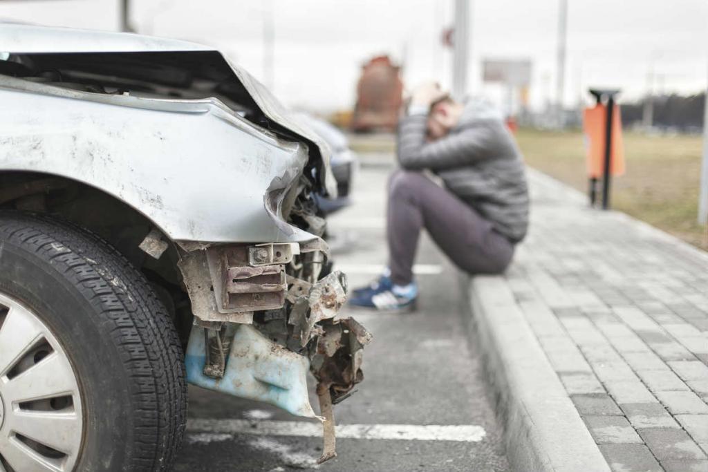 St. Louis man next to car after a crash
