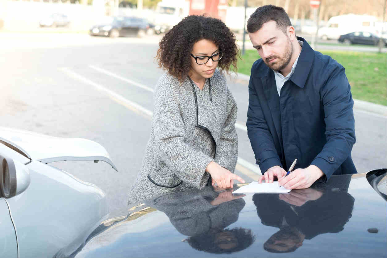 man and woman exchanging information after car accident