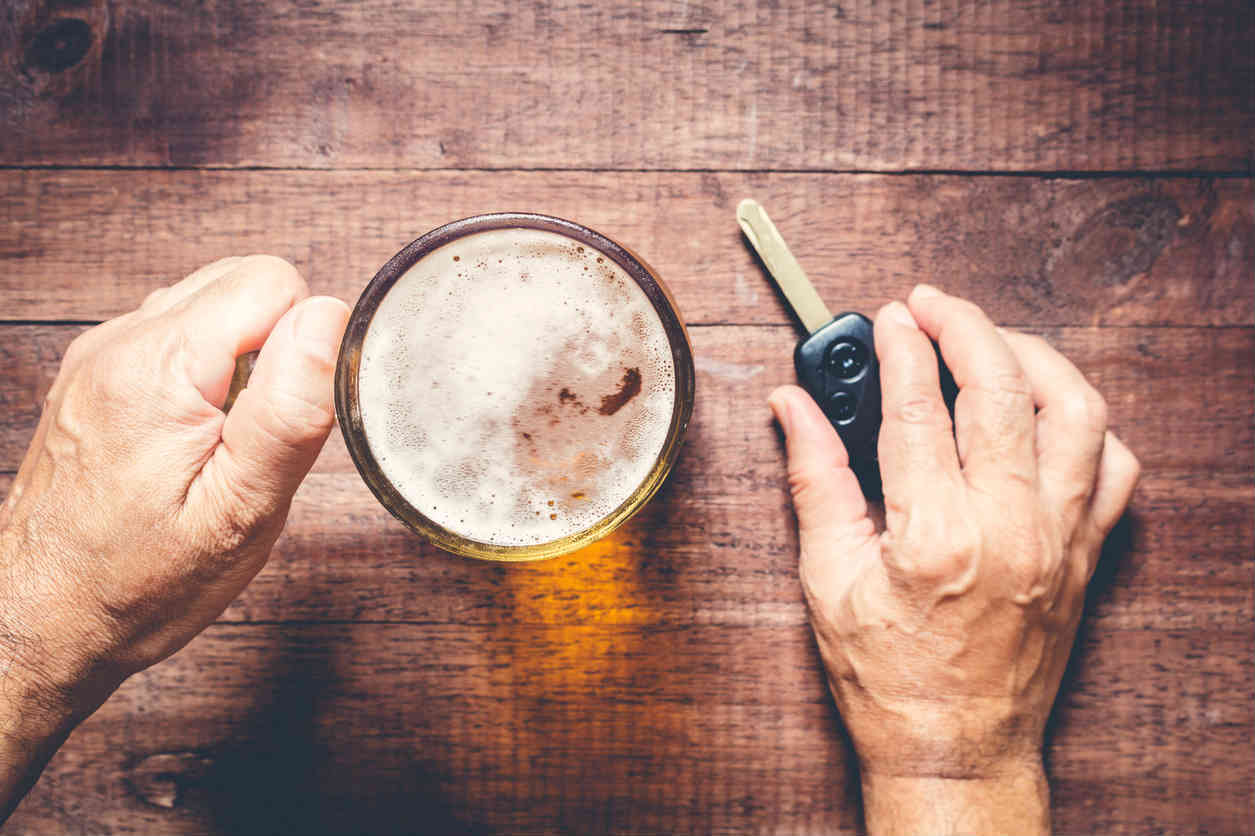 man holding a beer and car key