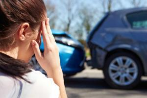 woman holding head after car accident