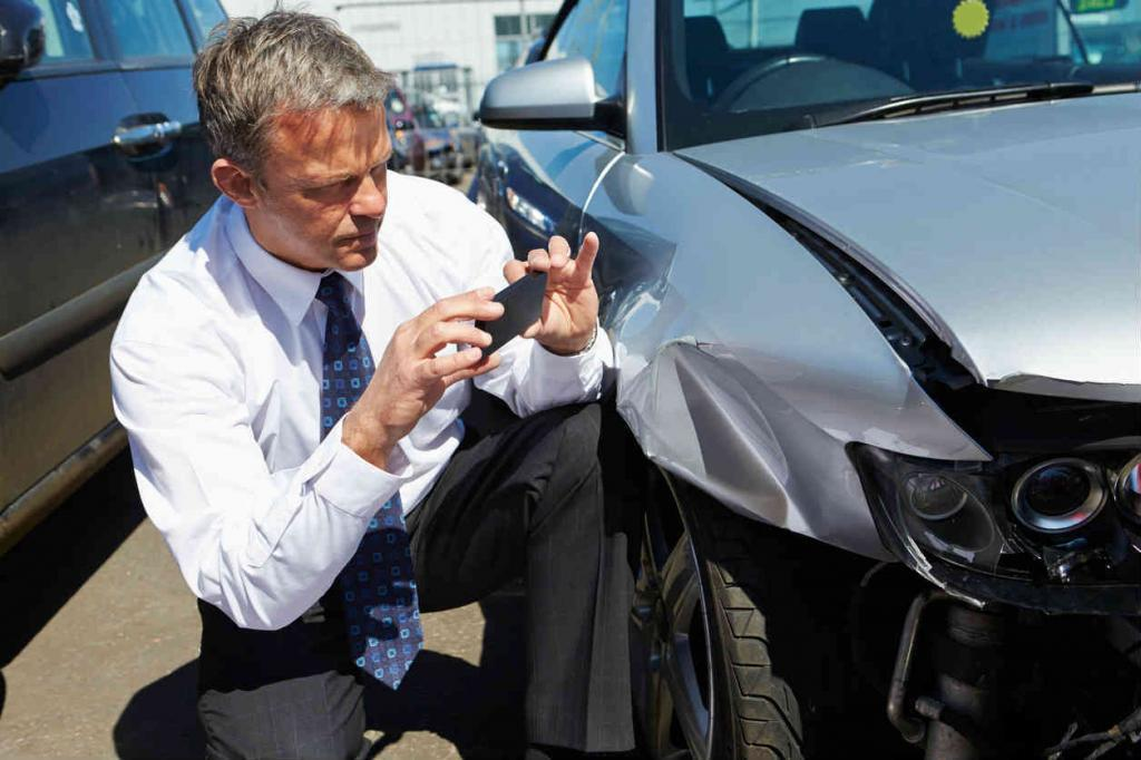 insurance adjuster taking pictures of car accident
