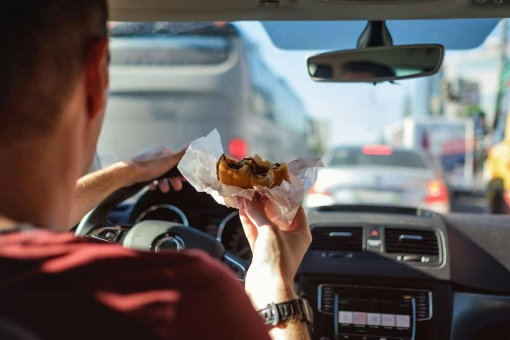 man eating a cheeseburger while driving