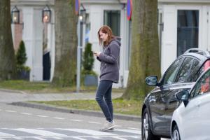 pedestrian walking in street texting