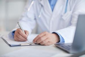 St. Louis doctor filling out medical record after car accident