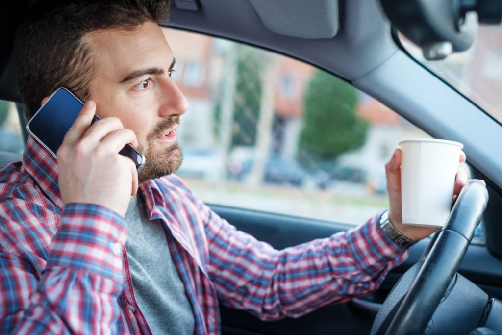 st. louis man using phone and drinking coffee while driving