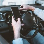 driver texting with one hand on the wheel